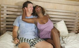 Mixed ethnicity couple in love cuddling together at home in bed with beautiful playful black African American woman and caucasian. Young happy and attractive royalty free stock images