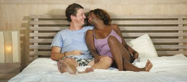 Mixed ethnicity couple in love cuddling together at home in bed with beautiful playful black afro American girlfriend or wife and royalty free stock image