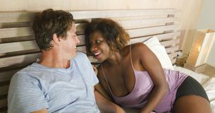 Mixed ethnicity couple in love cuddling together at home in bed with beautiful playful black afro American woman and caucasian. Young happy and attractive mixed stock photography