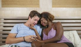 Mixed ethnicity couple in love cuddling together at home in bed with beautiful playful black afro American woman and caucasian. Young happy and attractive mixed stock image