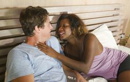 Mixed ethnicity couple in love cuddling together at home in bed with beautiful playful black afro American woman and white. Young happy and attractive mixed stock photos