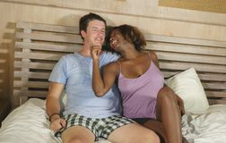 Mixed ethnicity couple in love cuddling together at home in bed with beautiful playful black afro American woman and white. Young happy and attractive mixed royalty free stock photos