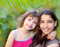 Mixed ethnicity cousin friends latin and caucasian. Mixed ethnicity cousin friends hug latin and caucasian in jungle garden Royalty Free Stock Image