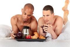 Mixed ethnicity gay couple. Attractive young mixed ethnicity gay, homosexual couple, Caucasian and African American men in the bedroom, grooming, enjoying Royalty Free Stock Photos