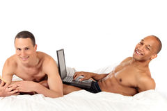 Mixed ethnicity gay couple. Attractive young mixed ethnicity gay, homosexual couple, Caucasian and African American men in the bedroom, grooming.  Studio, white Stock Photos
