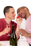 Mixed ethnicity  gay couple. Attractive young mixed ethnicity gay, homosexual couple, Caucasian and African American eating strawberry.  Studio, white background Royalty Free Stock Photography