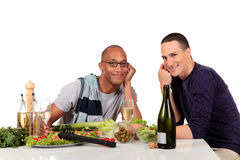 Mixed ethnicity  gay couple kitchen. Attractive young mixed ethnicity gay, homosexual couple, Caucasian and African American in kitchen, preparing salad for Royalty Free Stock Photo