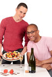 Mixed ethnicity  gay couple kitchen. Attractive young mixed ethnicity gay, homosexual couple, Caucasian and African American in kitchen, enjoying a fruit pie and Stock Photos