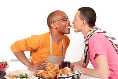Mixed ethnicity gay couple kitchen. Attractive young mixed ethnicity gay, homosexual couple, Caucasian and African American in kitchen, preparing breakfast Stock Photos