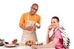 Mixed ethnicity gay couple kitchen. Attractive young mixed ethnicity gay, homosexual couple, Caucasian and African American in kitchen, preparing breakfast Stock Images