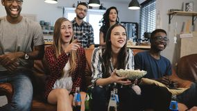 Mixed ethnicity group watching sports game on TV. Emotional fans on couch with drinks and snacks 4K slow motion close up. Togetherness. Entertainment and fun stock photo