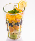 Mixed exotic fruits in blender. Mixed exotic fruits with leaf of mint in the blender ready to make cocktail Royalty Free Stock Images