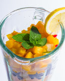 Mixed exotic fruits in blender. Mixed exotic fruits with leaf of mint in the blender ready to make cocktail Royalty Free Stock Image