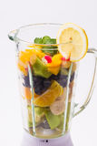 Mixed exotic fruits in blender. Mixed exotic fruits with leaf of mint in the blender ready to make cocktail Stock Photography