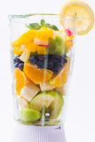 Mixed exotic fruits in blender. Mixed exotic fruits with leaf of mint in the blender ready to make cocktail Stock Photos