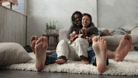 Mixed family with son sitting barefoot on floor stock video footage