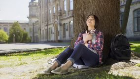 Mixed female reading book under tree, pressing it against chest, favorite book. Stock footage Royalty Free Stock Photos