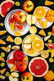 Mixed festive colorful tropical and citrus fruit sliced over bla Stock Photos