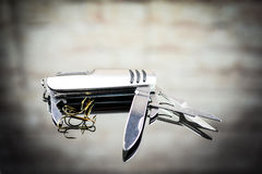 Mixed fishing lure and swiss army knife Stock Photos
