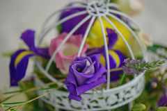 Mixed flowers arrangement with purple accents in a vintage decorative birdcage as a wedding table centerpiece Stock Image