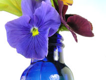 Mixed flowers in blue vase. Pansies with yellow iris in blue vase isolated on white stock photos