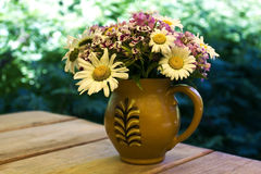 Mixed flowers in a clay jug Stock Images
