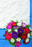 Mixed flowers in vase and sheet of paper Royalty Free Stock Photography
