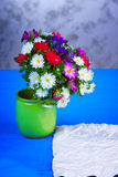 Mixed flowers in vase and sheet of paper on a table Royalty Free Stock Photos