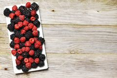 Mixed forest fruits as blackberry and raspberry on rectangular white plate, on rustic wooden background stock images