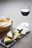 Mixed french cheese platter. With red wine glass and bread Royalty Free Stock Images