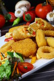 Mixed French Fries, chicken strips, onion rings. Mixed French fries, Nuggets, sausages and onion rings Stock Image