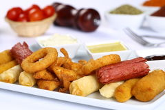 Mixed French Fries, chicken strips, onion rings. Mixed French fries, Nuggets, sausages and onion rings Royalty Free Stock Photo