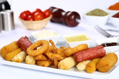 Mixed French Fries, chicken strips, onion rings. Mixed French fries, Nuggets, sausages and onion rings Royalty Free Stock Photos