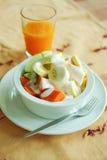 Mixed fresh fruits salad with yogurt and orange juice Royalty Free Stock Image