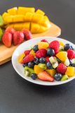 Mixed fresh fruits (strawberry, raspberry, blueberry, kiwi, mang. O) on white plate Stock Photo