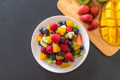 Mixed fresh fruits (strawberry, raspberry, blueberry, kiwi, mang. O) on white plate Royalty Free Stock Image