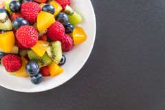 Mixed fresh fruits (strawberry, raspberry, blueberry, kiwi, mang. O) on white plate Royalty Free Stock Photography