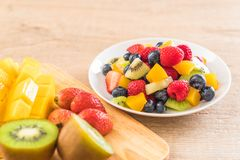 Mixed fresh fruits (strawberry, raspberry, blueberry, kiwi, mang. O) on white plate Royalty Free Stock Photos