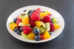 Mixed fresh fruits (strawberry, raspberry, blueberry, kiwi, mang. O) on white plate Royalty Free Stock Images
