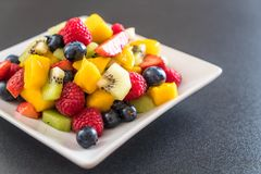 Mixed fresh fruits (strawberry, raspberry, blueberry, kiwi, mang. O) on white plate Royalty Free Stock Image