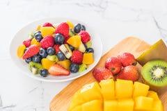 Mixed fresh fruits (strawberry, raspberry, blueberry, kiwi, mang. O) on white plate Stock Photo