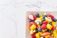 Mixed fresh fruits (strawberry, raspberry, blueberry, kiwi, mang. O) on white plate Stock Photography
