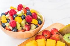 Mixed fresh fruits (strawberry, raspberry, blueberry, kiwi, mang. O) on wood bowl Stock Photo