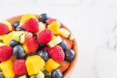 Mixed fresh fruits (strawberry, raspberry, blueberry, kiwi, mang. O) on wood bowl Royalty Free Stock Image