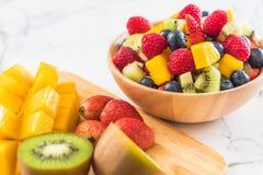 Mixed fresh fruits strawberry, raspberry, blueberry, kiwi, mang. O on wood bowl Royalty Free Stock Images