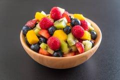Mixed fresh fruits (strawberry, raspberry, blueberry, kiwi, mang. O) on wood bowl Stock Image