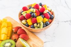 Mixed fresh fruits (strawberry, raspberry, blueberry, kiwi, mang. O) on wood bowl Royalty Free Stock Photography