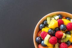 Mixed fresh fruits (strawberry, raspberry, blueberry, kiwi, mang. O) on wood bowl Royalty Free Stock Photos
