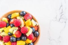 Mixed fresh fruits (strawberry, raspberry, blueberry, kiwi, mang. O) on wood bowl Stock Photography