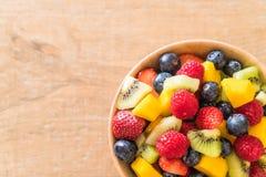 Mixed fresh fruits (strawberry, raspberry, blueberry, kiwi, mang. O) on wood bowl Royalty Free Stock Photography